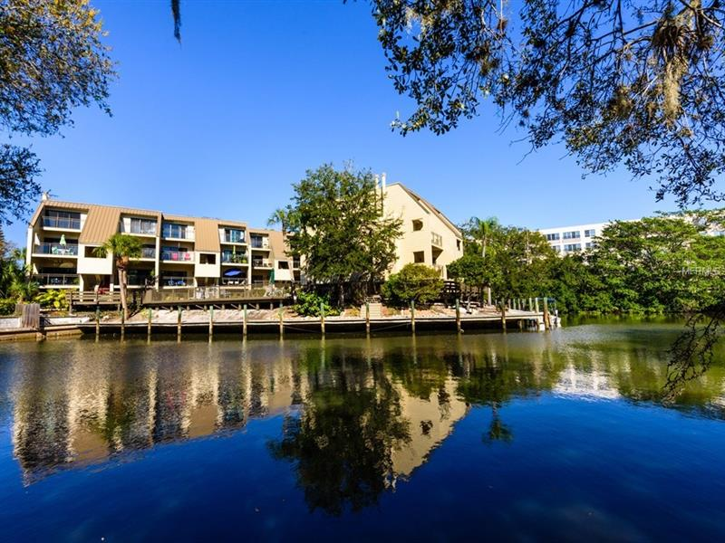 DOWNTOWN W/ UPPER FLOOR WATER VIEW!  Nestled on Hudson Bayou w/ 3 balconies.  Downtown Sarasota w/ canal access directly to the bay.  Quarry tiled flooring (2015) set on the diagonal throughout the 1st flr.  Great room layout combined w/ open, remodeled kitch.  Updated w/ raised ceil & inset lights, granite counters, a bkfst bar & island.  The furn quality wood cabinets w/ tiled backsplash.  Appls. include a refrigerator, a SS built-in microwave & range, plus a front load washer & dryer.  Also plumbed for a dishwasher.  Sliding glass doors present the bkfst balcony.  Full en suite & a waterfront MBr on 2nd flr.  It has a WIC, a built-in desk & sliding glass doors to its own pvt balcony.  Both bedrooms have new (2016) neutral carpet.  Bonus features include a newer A/C (2016), hurricane shutters, all glass sliders, a hurricane impact window (guest bedroom), an ext. storage unit & covered pkg under bldg.  Hudson Oaks is very stable, has excellent reserves & is well-managed.  Pet friendly zone (w/ a simple board approval) & leasing is OK.  There is a comm. pool, BBQ & a dock w/ 1st-come, 1st-serve access.  Accessibility for kayaks to meandering canals w/ hours of nature observing.  A secluded setting in an area known as Laurel Park, less than a .5 a mile to the Burns Court; w/ its cinema, shopping, galleries & dining.  Downtown location close to virtually every cultural event that the city has to offer & minutes to St Armands Circle, Longboat Key, & your choice of Sarasota's most beautiful beaches.