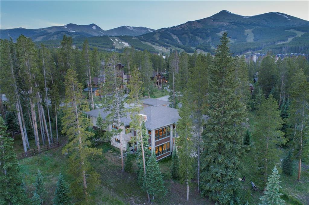 Perched above Breckenridge village, in a quiet, in-town area, this five bedroom home is within walking distance of Breckenridge ski resort.  The floor-to-ceiling windows envelop the entire great room, kitchen, dining, and entertaining areas with perfectly framed views.  This peaceful residence offers spacious main level living, complimented by intimate nooks, abundant fireplaces, and custom craftsmanship.  The walkout basement and second full kitchen, accommodate every multi-generational need.