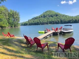 This lakefront property has it all.  The charming 5 br 5.5 bath cottage sits in a private wooded setting in a desirable neighborhood that is close to town.  It is a quality built home in good condition, with wood floors, fireplaces in the gathering room and master with great lake and mountain views.  A wonderful lakeside covered porch for dining and conversation as well as a screened sleeping and conversation porch make for inviting outside living.  The grounds offer a rare sandy beach perfect for kayakers and children and dock on deep water with lovely lakefront area.  The interior has views from each bedroom.  A paved driveway with plenty of parking on a large lot with room for an optional guesthouse makes this property a desirable spot for those looking for their special place on Lake Glenville.  This home offers space for a crowd with a bonus room and lower living area along with its five bedrooms and has an outstanding rental history.