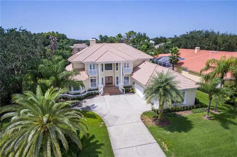 GREAT OPPORTUNITY!PRICE REDUCED!Beautiful luxury home, 6 bedrooms, 5 bath, office, possible wine bar area or play room area. The 6th bedroom is an In-Law suite. This top of the line home is located in the gated community of Presidents landing/Lansbrook. The home has many big windows with natural light, a formal living room with 26 foot ceilings, and a formal dining room with tray ceilings. The family room has an entertainment center that is adjacent to the kitchen. The kitchen has gorgeous mahogany cabinets, granite counter tops, a beautiful island, desk and marble back splash and GE Profile stainless steel appliances. Relax in this beautiful master suite, with gorgeous master bathroom with granite counter tops, rich wood cabinets and dual walk-in closets. There are 4 bedrooms upstairs. The master bedroom and in-laws apartment (6th bedroom with integrated kitchen) on the 1st level. Sliding doors lead to the screened paved lanai; relax by your spacious heated pool, recently resurfaced with Pebble Sheen Pebble-tec surface, and spill over heated spa. The Hayward pool equipment is fairly new; all controlled by remote access. There is a 3 car garage side entry. This home has been freshly painted inside and out. New electronic windows have been installed on 2nd level throughout and 8 surveillance cameras have been placed all throughout the property. It is in pristine condition!