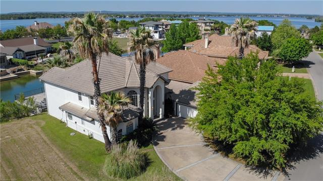 Majestic waterfront home in prestigious community on Lake LBJ. Magnificent great room with soaring ceilings, tall fireplace, wet bar, French doors leading to multiple lakeside patios. Kitchen with breakfast nook, formal dining & butler's pantry, master suite, office and powder room on entry level. Dual winding staircases take you to separate guest suites, one being a second master suite. Shared balcony. All bedrooms have lake views. Deck over boathouse, lakeside patio. 2 boat lifts and 2 jet ski lifts.
