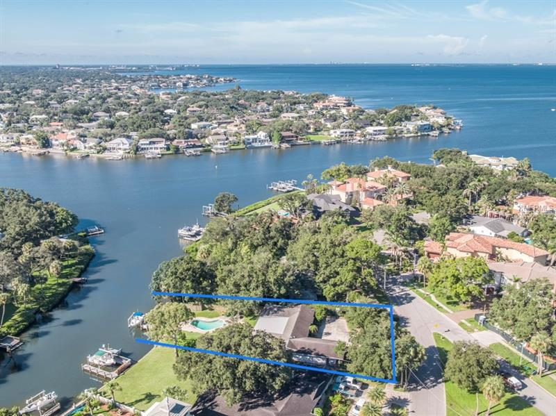 So many options with this prestigious Beach Park property—move in, renovate or teardown to build your waterfront dream home! 70 feet of wide canal waterfront only 6 homes from Open Bay with 201 feet of depth offering over 1/3 acre of space for any buyer's needs.  The current one-story home is 2425SF with 3 bedrooms and 2 bathrooms and offers an open floorplan filled with natural light.  Wood flooring can be found throughout the living space with high ceilings to add a contemporary casual feel.  The outdoor space offers a screened lanai, pool and open patio on the way out to the dock and boat lift.  The quiet street and neighborhood are brimming with luxury waterfront homes.  This is perfect for the discerning buyer who wants to customize a 1961 mid-century ranch or build their own ideal home.  The location is unique as it offers a serene tucked away feel yet is close to Tampa International Airport, shopping malls, movie theaters, interstate access, abundance of restaurants and Downtown Tampa.  Get ready because the sunsets will take your breath away!!!