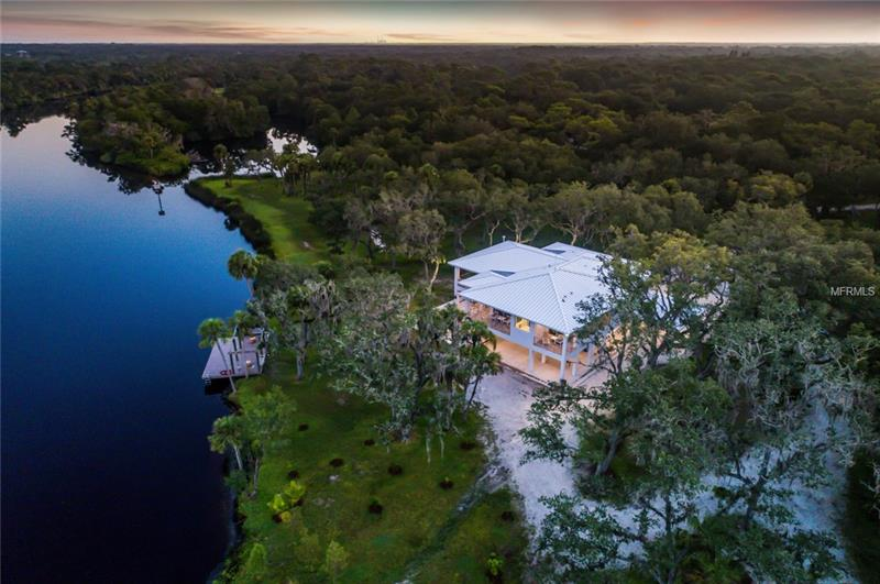 Breathtaking Old Florida property with custom contemporary lifestyle. This one of a kind builders' home has it all! The ultimate in privacy like you have never experienced before. Boasting over 7 acres and 1400 feet directly on the Manatee River and 3 docks that have power, wi-fi, water and Sono stereo system.  Once you enter this home you will be impressed with the state-of-the art features. Custom solid wood cabinetry, Italian tile and marble in all baths and main flooring throughout the house, decks and stairwells. The kitchen is outfitted with Wolfe range, Subzero refrigerator and wine coolers as well as Viking, Meile, Sharp, Whirlpool appliances and Kohler plumbing fixtures. Built with first class energy efficiency with hurricane level construction. Commercial grade foundation with auger cast pilings. Wrap around decks and PGT/ Winguard windows provide the ultimate views and safety. This two-story home has a metal roof, 37' Auger cast pilings and solid concrete walls, an elevator, full house generator, 1000-gallon propane tank and freshwater well.  The outdoor kitchen has it all including smoker, grill, burners, poured concrete table, sink and bar.  Every detail in this home has been well thought out professionally executed. The construction was completed earlier this year. This is certainly a home that is well worth the consideration.