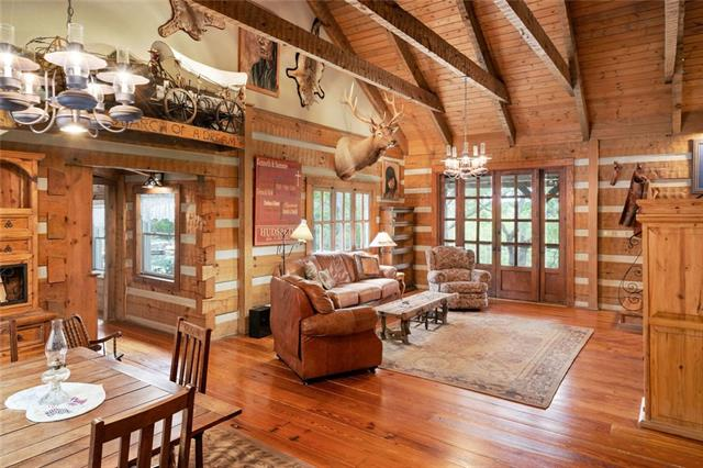 Hidden away on this 51-acre pastoral landscape, just minutes from Wimberley, is one of the finest quality timber-framed log homes to be found. This 4 bedroom, 31/2 bath home has perimeter walls of hawthorne pine logs, 100 year old pine floors, a front porch for relaxing, and a rear deck leading to a beautiful pool/spa/patio area. The adjacent Livery contains a 3 bay garage, a workshop, storage and a fine guest apt. All on over 50 acres in 3 tracts, with wildlife exemption. 24 hour notice for showing.