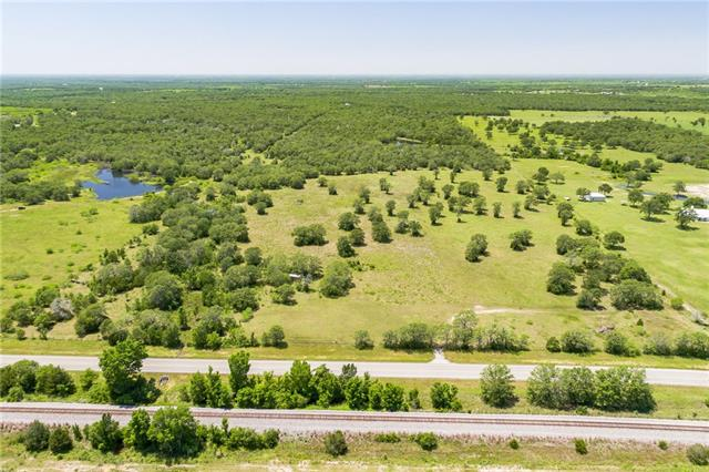 Abundance of water & wildlife on FM 154, county maintained paved road. 1 of only sites this close to town w/ideal rectangular shape both open & wooded w/ponds & 5 acre lake! Large open prairie near entrance & 70% oak tree wooded in back w/good trails for exploring, hunting, ATV. 100% fenced w/stocked pond/tank over 1.5 acres along w/couple of other smaller ponds to west w/woods which makes great habitat for deer & wildlife. Soils of singleton fine sandy loan w/slopes of 1 – 3%. Small barn & cattle pens.