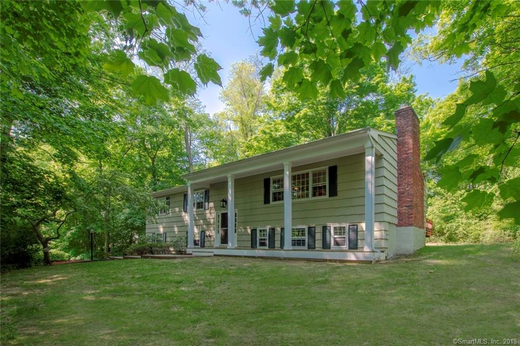 Privately set 3 bedroom home with beautiful wooded views minutes from schools and the village. Sought after open floor plan with spacious updated kitchen opening into dining and living room with fireplace and two sets of sliding doors. Huge deck runs the length of the house for outdoor entertaining. Lower level boasts large family room with new wood look tile, and fireplace, office and bath. Lovely Master Bedroom has full bath and also has sliders to the deck. Deeded Lake Rights to Mamanasco Beach club also included for summer fun!