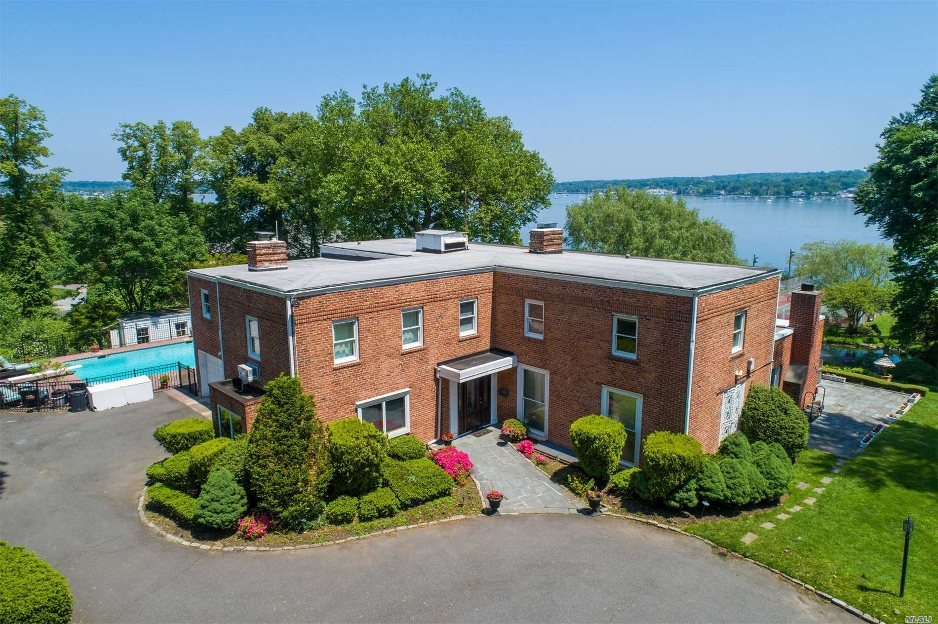 Amazing Waterfront Brick Colonial On A Private Beach Facing Manhasset Bay. Set On A Lush 4 Acres, Landscaped Compound, Including Fresh Water Pond, Tennis Court & Heated Pool. Large Entertainment Area - Family Room, Living Room, Dining Room & Library, Finished Basement. A True Gem. Convenient To Nyc.