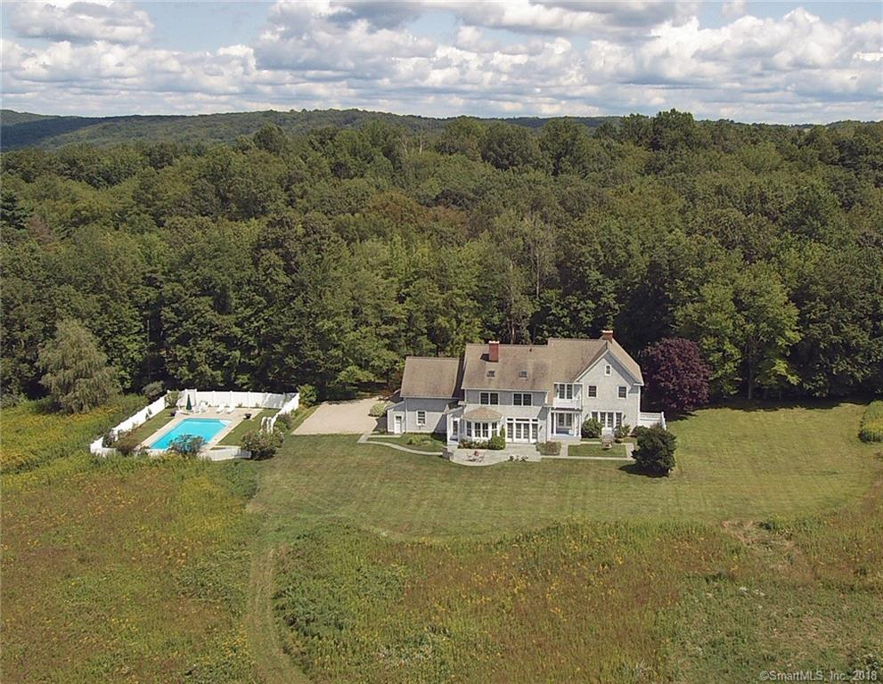 Unparalleled perfection awaits. One of a kind home & setting on most picturesque, private, & level 5 acres w/circular drive, mature landscaping, heated in-ground pool, fenced in vegetable & cutting gardens, scenic meadow w/walking path & impeccable shingle style custom colonial. Highest attention to detail inside & out this nearly 4,500 sf elegant home w/designer appointments incl. wide board pine floors; 3 Rumford fireplaces; custom mill-work incl. moldings, wainscot, coffered ceilings, built ins; & multiple French doors to the outdoor stone patios, pool, & gardens. The main floor features an open floor plan w/wide front to back foyer & sweeping stairway open to the LR offering limestone fplc for cozy nights & French doors to the rear stone terrace for outdoor enjoyment; formal DR; private library; & most inviting FR with stunning river rock fplc. The expansive chef's kitchen features a bright breakfast area, island w/bar seating, professional appliances, & charming brick fplc. The 2nd floor features an impressive landing w/French door balcony overlook; sophisticated MBR suite with spa-like Limestone bath & custom dressing room; 3 additional spacious bedrooms w/built-in window seats; plus the vaulted bonus room, ideal for fitness, media, or play room. Enjoy built-in audio system, whole house generator, & sought after West Redding location, convenient to trains, restaurants, shopping, & commuter routes, approximately one hour to NYC. Don't miss the virtual tour & floor plans.