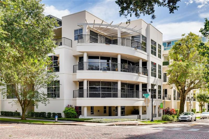 Unique contemporary downtown condo directly overlooking Lake Eola Park with a wrap around balcony on second level, a large private walled porch at street level, and floor to high ceiling windows on both levels.  2500+ sq feet -- 3 bedrooms 3 baths PLUS office. Unit has Split floor plan with master bedroom and bath with walk in closet lower level along with additional bedroom. First floor also has sitting area with private exit directly onto porch (great for walking the dog or strollers to the park), office with pocket doors and laundry room. Upper level has kitchen with stainless steel appliances and granite counters, living/family room with panoramic floor to ceiling windows overlooking Eola Park, dining room and third bedroom/media room and third bath with shower. Floors are tile and wood. Unit offers TWO secure inside parking spaces.  This unit has LOCATION LOCATION LOCATION.