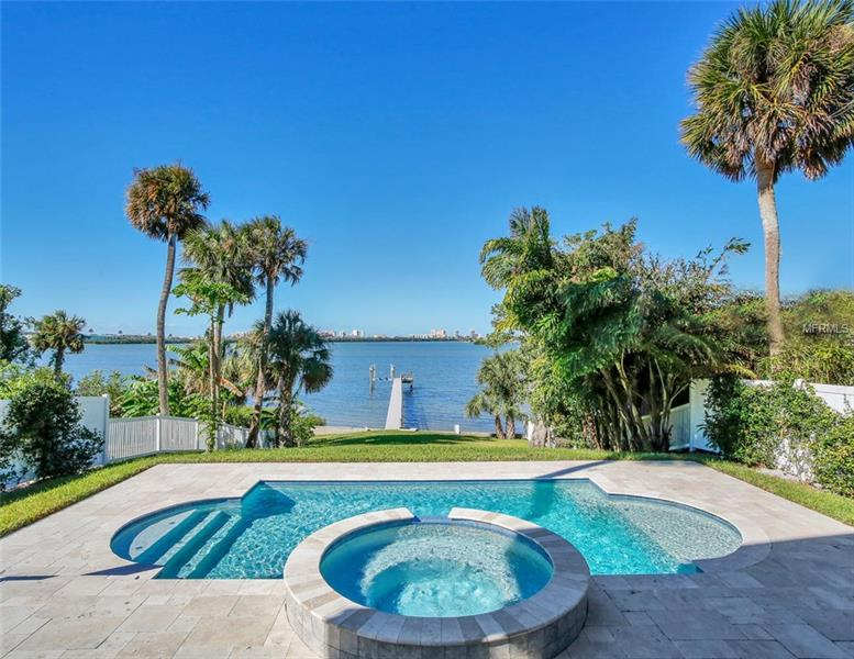THE ULTIMATE IN COASTAL LUXURY AWAITS. Custom built in 2014, this waterfront estate of 4,090 sq ft is the perfect blend of craftsman architecture with modern coastal design. The 282' deep lot rises from the Intracoastal Waterway to a bluff where the home is located above the flood plain providing amazing open water views. A luxurious great room provides the ultimate open living & entertaining space with a dining room, living room, family room & kitchen combination featuring travertine & hardwood floors, double-sided gas fireplace & 3 sets of French doors opening to the covered lanai & open water views beyond. The family chef will enjoy the stainless appliances with 6 burner gas stove & wine refrigerator. A prep sink sits in the expansive kitchen island with gorgeous granite & seating for 5+. The master suite spans the entire water frontage with wood floors, French doors out to a covered balcony, travertine-clad bathroom with jetted tub, dual sinks & walk-in shower & large walk-in closet. 4 spacious guest bedrooms & bathrooms are perfect for family & guests. A media/game room acts as a 2nd floor family gathering room. The backyard oasis features a large covered lanai & beautiful heated pool & spa with travertine decking. An expansive lawn leads down to the 152' composite dock with boatlift. A 2 car garage, camera security system & gorgeous laundry room round off the features of this incredible estate. Surpassing the latest hurricane codes & an elevated lot allows this estate to enjoy low insurance costs.