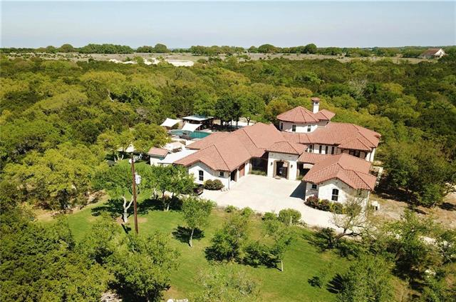 Lavish country home nestled amid canopy of trees w/hill country views. Close to amenities & 30 min to Austin. Includes large open living areas w/vaulted ceilings, chef's kitchen & dining area, large bedrooms, master suite w/walk-in shower & closets, theater room, bonus room & 1 bed/bath guest suite. Luxury living perfect for family or business owner. See MLS#8758903 for commercial adjacent property - 2.5-acres which is negotiable to be subdivided & included in this sale making it approx a 5-acre property.