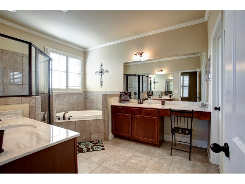 Gorgeous master bath boasts separate vanities, spacious shower, garden tub, beautiful granite & custom tile!