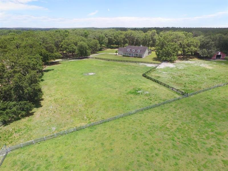 Fabulous 20+acre horse ranch...a peaceful country setting w/city convenience! This home is a horse lovers dream: 7 fenced pastures each w/water, a 16 stall barn w/tack room, wash bay, 1500 metal storage building & hay room. This 3,488 sq ft 2-story home has a huge front porch, 4 bedrooms, 2 ½ baths & is surrounded by massive oak trees & a private entry gate. As you enter the double doors into the foyer you will enjoy gorgeous hardwood floors & soaring ceilings. The kitchen is a chef's dream, boasting a Wolf sub-zero refrigerator-freezer, built-in wine cooler, stainless appliances, double wall ovens, granite counters & backsplash, plenty of rich cabinetry & breakfast bar. The adjacent great room enjoys a wood burning fireplace & French doors that lead to the paved, covered & screened lanai w/salt water pool w/sun shelf. Enjoy Florida living at its best on your 90K private patio, screened lanai, pool deep enough for diving & outdoor kitchen! The master bedroom suite features French doors leading to the pool, custom closets, granite counters, new ceramic tile that looks like wood, relaxing garden tub & upgraded dual sink vanity. This home enjoys a true split-plan. The 4th bedroom is presently used as an office, the sellers will replace the cabinets with a closet at the seller's expense. You will enjoy an enormous bonus room upstairs! Beautiful hills close to major roads that connect you to shopping, entertainment, hospitals & beaches, yet far enough away to enjoy the private Dade City hillside. Welcome home!