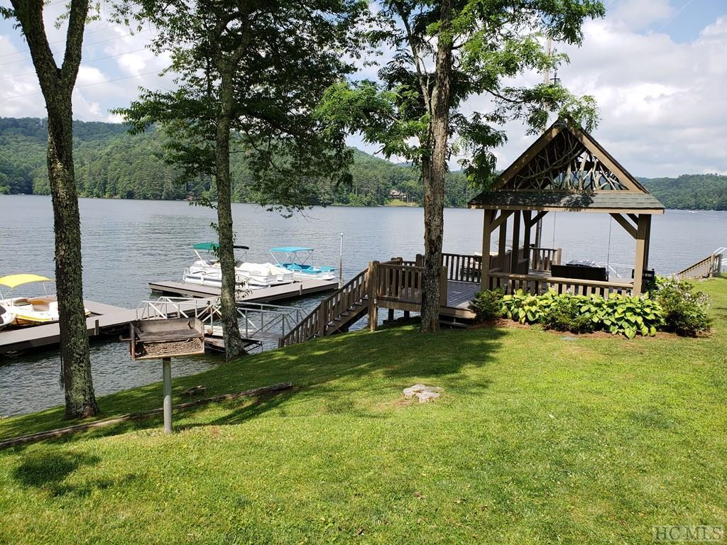 "Fabulous Lake Glenville location overlooking your boat slip in Cedar Point Landings and an  expansive view of one of the widest sections of Lake Glenville and the mountains beyond. Imported from Germany, the entire lower section of the wall of glass overlooking the lake opens accordion style transforming the living room to a virtual outdoor space with two fireplaces, one wood burning and one gas log, to make this experience complete. A newly remodeled kitchen on the main floor is a chefs delight with an additional kitchen in the apartment or mother in law suite below. The huge master bedroom currently houses 2 queen size beds and a sitting area complete with chandelier and gas log fireplace. Accessible  from the master bedroom or the living room you will find a uniquely decorated screened room about 50 feet in the air creating a ""tree house"" feeling with the lake in the background. From the upstairs bedroom, step out on the rounded indoor balcony overlooking the living room and beyond the open wood beams and unique chandelier, the view through the wall of glass is impressive. Shown by appointment only."