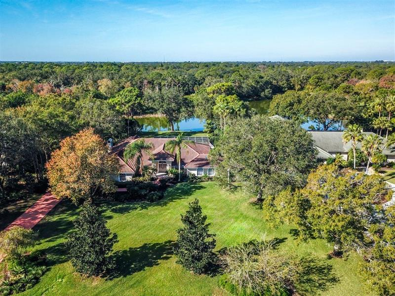 PRIVACY W/ LAKE VIEWS ON NEARLY AN ACRE!  This is a spacious home w/ 3Br, 3Ba, office, formal Lr & Dr plus a kitch. w/ a bkfst nook & a comb fam rm.  Boasting custom ceil, skylights & detailed woodwork; crown mldgs, ceil medallions, chair railings, wainscoting & built-ins.  Vaulted ceils & in formal Lr w/ triple SGD.  HW flrs in the Lr & Dr w/ a granite wet bar.  Kitch./Fam Rm/Bkfst nook w/ granite, bkfst bar, lg. prep area, wood cabinets, task ltg, pantry, tile, SS appls., vaulted ceils, crown mldgs & wood burn fp.    MBr is over 500SF w/ a sitting area, a tray ceil & dbl walk-ins.  MBa w/ granite, wood cabinets, dual sinks, diagonal tile, a jetted tub & a sep shower.  French doors provide privacy in the den or study w/ a nearby Ba.  The split plan layout also includes two additional bedrms & a third bath w/ dual sinks & a pool entrance.  Multiple sets of SGD access the huge screened & paver lanai w/ a covered entertainment area, a pool & a spa.  A side-entry 3CG, a tile roof & tropical landscaping offer fantastic curb appeal on a pvt lakefront lot w/ nearly an acre.  Poised elegantly in the comm. of Ashley, one of the hidden gems of east central Sarasota, the property is centered among 50 private & wooded home sites set amongst three serene lakes. The location is simply idyllic: close to area beaches, great schools, championship golf, & a variety of shopping & dining options.