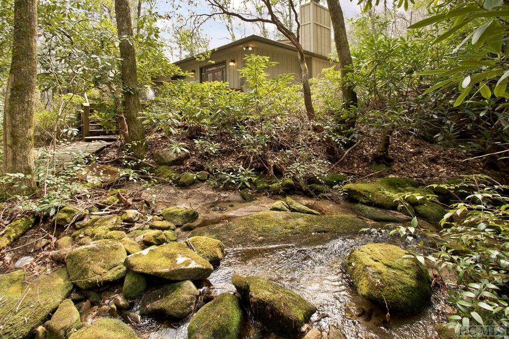 This home is Creekside/waterfall side with privacy sited on 5.87 acres in Holly Berry Estates. Almost every room takes view advantage of the swiftly flowing creek. There are 2 beautiful wood burning fireplaces - 1 in the living room and 1 in the master suite. The layout of the house is perfect for families with the main level having the master suite and guest suite, open living area and large deck overlooking the creek. The lower level has its own family room and covered deck overlooking the creek with a great bedroom and extra bonus room. Small trails meander through the property to explore and take advantage of the creek and waterfall. The land lays very gently. There is plenty of flat space for a garden area. Holly Berry also has 2 beautiful lakes for owner use. This would also make an excellent vacation rental home.