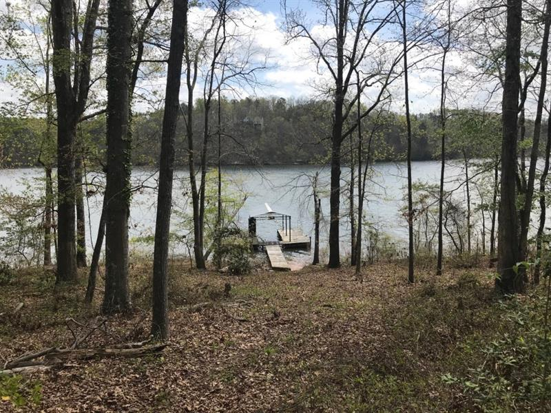 Brand new offering for Lake Lanier waterfront lot. Lot has been subdivided from a larger property. Lot lays perfectly for a new home to be built near the water. Wonderful views. Single slip covered boat dock in place. Property is located along the Olympic Rowing Course just a few hundred feet from the finish line and finish tower. From your dock you can have the million dollar view of local and world class racing competition! Located 3.5 miles from Don Carter State Park.