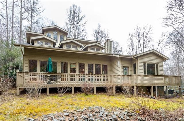 This home is a peaceful mountain retreat sitting on several wooded acres up a mountain road with two creeks that come together right in front of the house. The home is architecturally designed with an eye towards beauty and spaciousness with floor to ceiling windows overlooking the creek. The floorplan is very open, and includes a formal dining space, along with a breakfast nook. Also on the main level is a library, and a spacious master bedroom. The second level includes two bedrooms, and two full bathrooms. The third level has a cozy solarium, perfect for reading and relaxing. Outside, sit on the spacious deck and enjoy nature, or follow the bridge across the creek to the gazebo. The two lots across the street also convey, so you have even more privacy. This is the mountain getaway of your dreams!