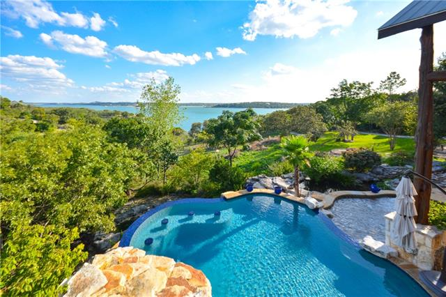 Incrediblely private estate on Lake Travis! 20+/- acres on deep water with incredible, big lake views. A wooded, winding drive takes you to the lodge style luxury home featuring an attached guest apt, enormous great room with towering cedar-beamed cathedral ceilings, floor to ceiling windows and gourmet kitchen. The custom pool has a hot tub, waterfall feature, and is complimented by surrounding koi ponds and water features. A gentle slope takes you to the water and boat dock. Addt'l acreage available!