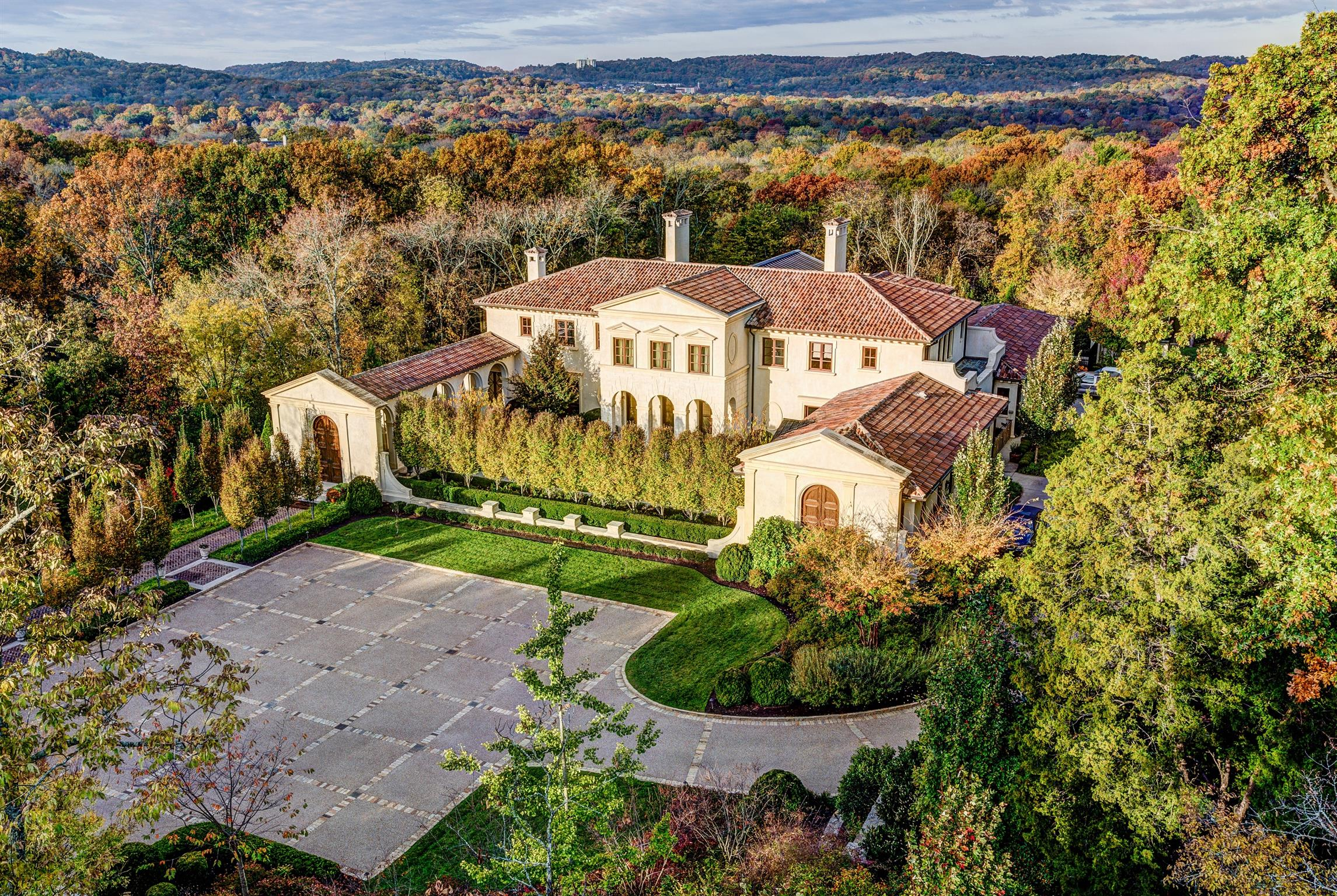 Nestled into the rolling hills of the landscape, this Palladian/Neo-Classical proportioned residence was heavily influenced by Santa Barbara Spanish Colonials popularized in the early 1920's & 30's Steel framed, brick veneered, then in stucco with hand-cut limestone accents and barreled tile roof. Marvin mahogany windows & doors thruout.