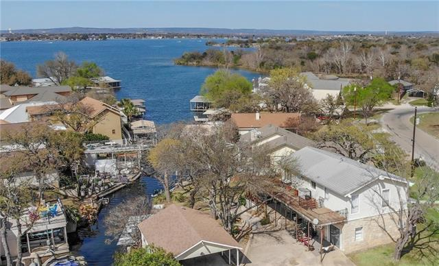 Lake LBJ waterfront home with terrific open water views, situated on a short cove! Along the approx. 85 feet of waterfront stretches a boathouse, fishing dock, and a jet ski lift. Unique 2-story home with large living areas and huge decks on each level, overlooking the lake. Each level boasts a large living area, bedroom, and bathroom. Private outdoor access from both levels. 2-car carport with workshop and storage. Located in the serene neighborhood of Oakridge Estates adjacent to Horseshoe Bay Resort.