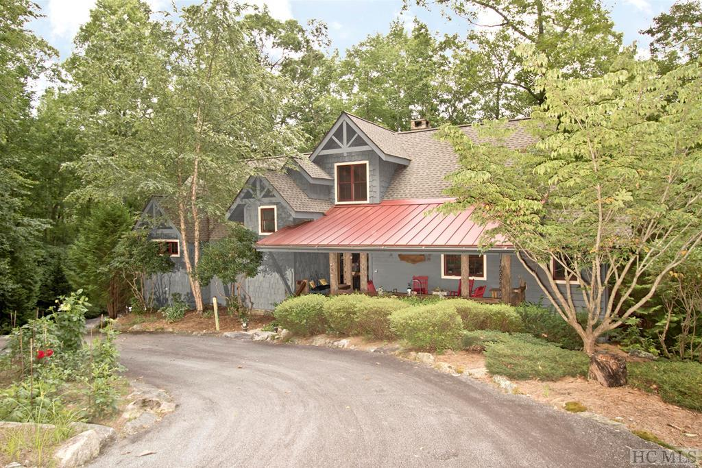 This wonderful custom built family home is close to downtown Cashiers with a park like setting on 1.33 acres. There are 4 bedrooms and 3 1/2 baths plus a loft area.There are many beautiful features of this home, including granite countertops, hardwood floors, cathedral and beamed ceilings, wet bar, 2 fireplaces - 1 in the great room and 1 in the master bedroom. The kitchen features an island with stool seating for cozy dinners. Some of the outdoor features include 2 screened porches, plus a deck with surround sound, and front porch to add several outdoor entertaining areas. The layout of the home is perfect for just a few or many guests at a time. It has been meticulously maintained. Several trails are on the property which meander down to the stream which is part of the headwaters of the Chattooga River system. A stocked trout pond adds to the many reasons to live in this scenic neighborhood which is only 1.1 miles to the center of town.