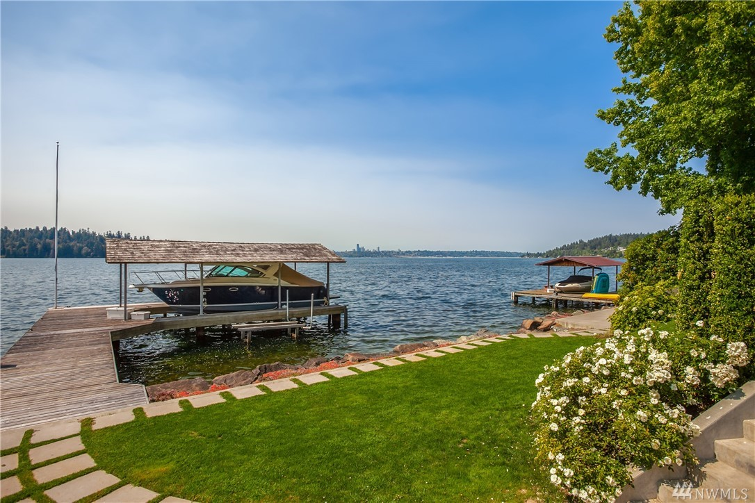 This one will take your breath away!  107' of stunning westside waterfront with unparalleled views of the mountains, lake and skyline. MI's most desired address! Original 1948 home has been thoughtfully updated & expanded. Crisp interiors married with warm woods & walls that open.  Dreamy master suite offers a front row seat to the changing views.  Second master on the main offers versatility.  Extra private parking area makes entertaining a breeze.  Deep moorage with 30' covered slip.