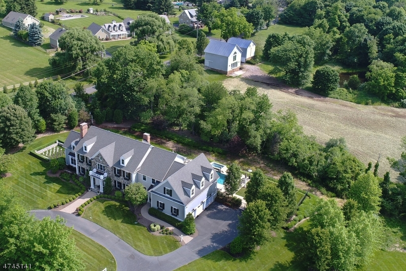 A stately, stone-accented manor home is a gracious presence at The Ridings, one of Tewksbury Township's  premier neighborhoods. The sun-splashed open floor plan of 7,048 square feet on the first and second levels is enhanced by an additional 2,000 square feet of living area in the beautifully-finished lower level. A total of five bedrooms, five full and two half baths are well-appointed. Set on over five acres, the property presents a pond, an in-ground pool, two outdoor kitchens, a granite patio, rear courtyard patio with hot tub, outdoor chess area and two early 1900s barns, one for tractors and the other beautifully renovated in 2008. Highlights of the impressive floor plan include oak hardwood, marble and ceramic tile flooring, round, tray and cathedral ceilings, recessed lighting, a second staircase, expansive chef's center island kitchen, butler's pantry, two wet bars, dining room with cove lighting, cherry paneled library with gas fireplace, music room/den, cathedral ceiling great room with fireplace, master suite of rooms and walkout lower level finished with fabulous gathering areas. The mostly finished and heated lower level has wet and dry bar areas with a temperature-controlled wine cellar, media, game and billiards areas, exercise and craft rooms, plush unfinished storage and utility rooms. A full bath contains an oversized tiled shower enclosed by frameless clear glass doors. Storage needs are easily met in the three-car oversized garage with automatic door openers.