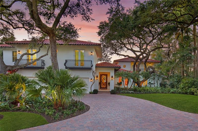 A testament to the classic refinement and tropical ambiance of coastal living, this Bayfront estate is situated on almost one acre with 180 feet of water frontage. Completely renovated/expanded in 2017, savor unobstructed vistas of Roberts Bay and the Intracoastal where magnificent sunsets remind you to stop and enjoy the view. Set back from Red Rock Way, you'll appreciate complete privacy. The stunning entrance leads past the library to the elegantly casual living room, with French doors, custom coral gas fireplace, and French oak floors. The dining room and large covered terrace are just steps away, with coral floors and a pecky cypress ceiling. The kitchen showcases custom cabinetry of painted wood and natural walnut, Calcutta gold marble and quartz, Thermador appliances, immense island, and wet bar. The family room, with wood-burning fireplace and French doors, leads to a terrace. The master bedroom is completely private and spacious with vaulted paneled ceiling, large covered terrace, his/her baths, outside shower and oversized closets. The second-floor features three en suite bedrooms while the fifth guest suite is completely separate. The focal point of the backyard is the heated pool with spa, along with fresh, new landscaping, century old oaks and mature palms. The waterfront dock is perfect for casual boating, water sports, fishing and watching the sunsets. West of the Trail, you are only moments from world class beaches, cultural activities, culinary pursuits and sporting adventures.