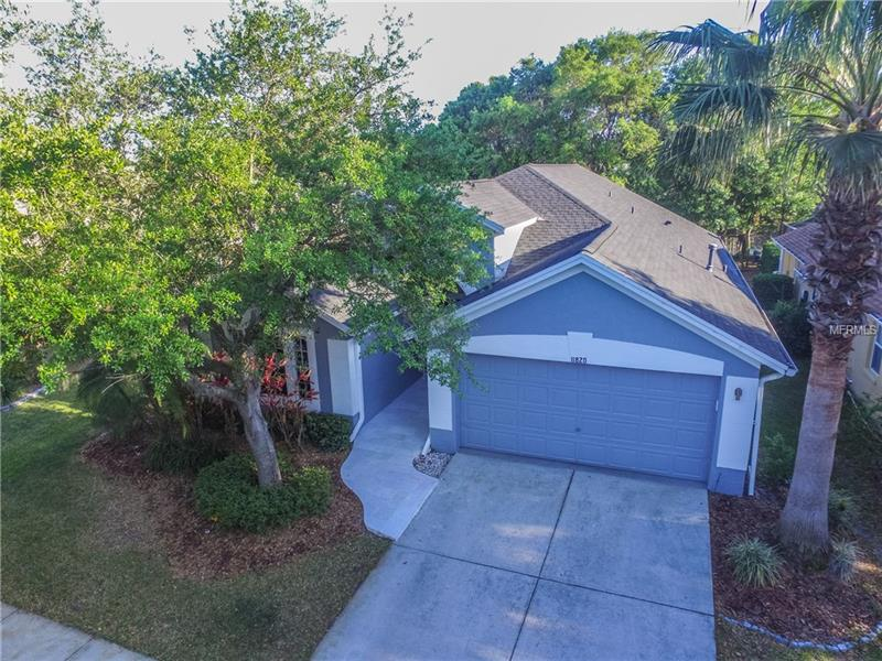 """Serene waterfront view. Natural light abound. A turn-key home in the highly desirable """"Shires"""" neighborhood of Westchase. 11820 Easthampton is designed to thrill while priced to sell! 3 bedrooms, 2 bathrooms, and a 2 car garage. NEW ROOF in 2014. The decorator paint and cathedral ceilings throughout are truly refreshing. The updated kitchen boasts granite countertops, oak cabinets, and stainless steel appliances. Cook up a storm, and then relax with a hot coffee- perched on the breakfast bar. This space is perfect for entertaining, as the kitchen opens up to the family room- and the party can be extended all the way to your screened patio & backyard-which boast STUNNING views of the private lake. This home also boasts a separate formal living room for receiving guests,a formal dining room, and two spacious secondary bedrooms. Elfa Closet system throughout including garage. The split floor plan allows privacy for the master suite & a master bath which features an oversized garden tub, separate shower, and double vanities. Laminate wood floors & ceramic tile throughout. Finished garage flooring. WELCOME to a PRIME location, with A-Rated schools, golfing, community events, and walking distance to restaurants, grocery stores, library and playgrounds. Come make this house a home."""