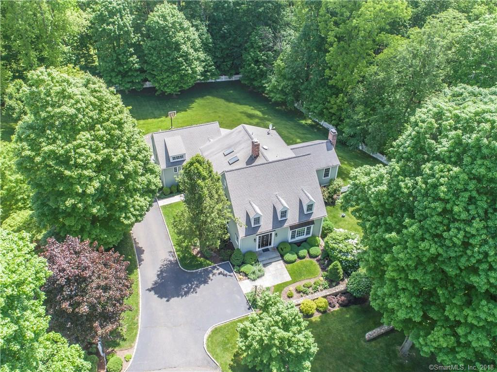 """With very close proximity to Downtown Ridgefield, this stylish and sophisticated classic New England Cape features a park-like setting and is beautifully sited on one of Ridgefield's most desirable cul-sacs.  Built in 2002, the home boasts many top quality details and showcases a wonderful open floor plan spanning 3 beautifully appointed floors. Gracious open foyer, spacious Living Room and Dining Rooms, designer """"white"""" Gourmet Kitchen w/Breakfast Room open to fabulous vaulted Family Room w/floor to ceiling stone fireplace + French doors to 2-tier Mahogany deck. Handsome Library with built-ins, large Mudroom, Laundry Room plus a fabulous Master Bedroom Suite with spa-like Bath and His/Hers closets round out the first floor. The upper level features a wonderful open lounge area with an add'l Master Bedroom Suite option, 2 additional Bedrooms and a large bath.  Fabulous Walk-out LL has Games Room plus a second Family Room with Fireplace, Guest Suite w/bath (perfect for AuPair or in-laws) and lots of storage. Stunning grounds w/stone walls, prof. landscaping, irrigation system & room for pool. Town Water.  Super Commute Location - Approx. 1 hr to NYC by car and easy drive to Katoonah Train Station or just minutes to the shuttle in downtown Ridgefield with service to the Katoonah Train Station. Turn-key condition.  Start living the dream in Connecticut's #1 Town with award winning schools. The cultural and recreational amenities are endless."""