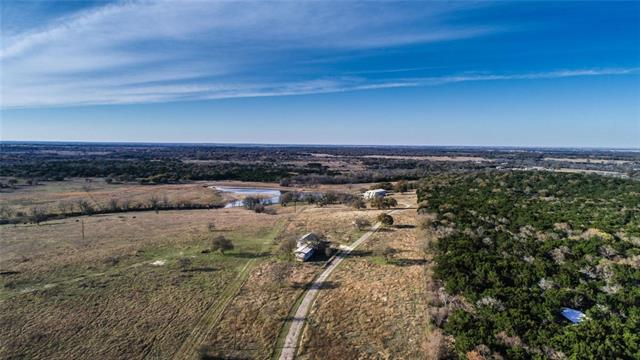 2 Parcels sold together.  Great possible commercial property- event/wedding venue, RV park, distillery/brewery, or cattle operation.  Property includes, home built in 1970, with garage/workshop,  guest house, and two barns. The largest barn is 40x80 and is two stories with upper loading capabilities.  Downstairs has two smaller 30x40 barns with another bathroom.  Home and barns overlook a neighboring pond for an idyllic hill country get away. 1 well and 2 septics currently on property