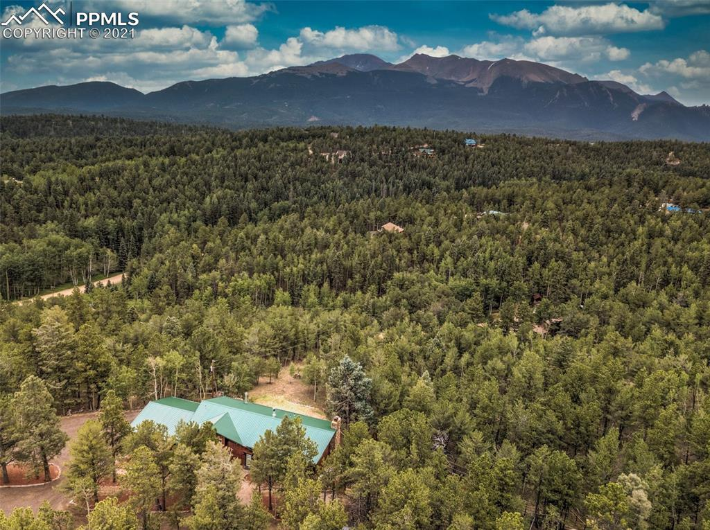 Amazing Pikes Peak view home on 2+ acres, 10 minutes from Woodland Park. This huge home has 3 bedrooms, 3 baths, with 2 kitchens, 2 family rooms, 2 offices, and 4 fireplaces! Fenced off area for your pets. Oversized garage with work bench. Huge, 56 foot deck. Hot tub and sauna included. Remodeled bath and room for more of your own touches. Luxury vinyl planking. New carpet. Private, cul-de-sac location.