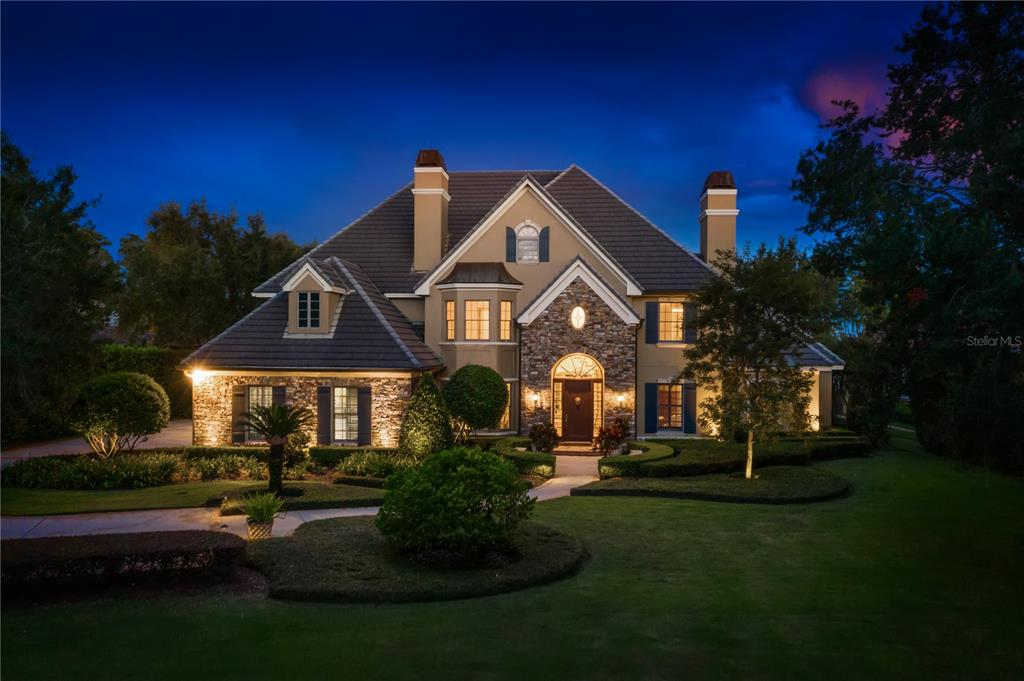 Exquisite lake front masterpiece, located in the 24-hour guard gated community of Keene's Pointe. This home is perfectly positioned on one of the best lake-front lots in the neighborhood, with over 2 acres and expansive Lake Tibet views. Luxury and elegance resonate throughout this one-of-a-kind lake front estate. From the stunning European architecture to the elaborate details, like the solid mahogany front door, custom stonework, and English cast stone benches on the exterior to the solid wood beams and intricate finishes on the interior. As you step through the front door of this Akers custom home you are immediately greeted by soaring two story ceilings and amazing lake views. The first-floor master suite features a large sitting area with windows overlooking the pool, his and hers closets, and a spa bath with a large walk-in shower and oversized tub for soaking away the stresses of the day. The recently updated kitchen features stunning quartz countertops, top of the line appliances, and a large eat in breakfast area. On the first floor you will also find formal and informal living areas, a large dining area with a fireplace, a study, and a guest bedroom suite. On the second floor you will find a huge game room overlooking the expansive grounds, a theater / bonus room, 4 additional bedrooms, 3.5 baths, and even an English phone booth. Exterior amenities include a whimsical butterfly garden with stone walkways, an incredible pool area with a hot tub that spills water into a lazy river leading to the pool, an amazing summer kitchen with outdoor TV area, a pool bathroom, and of course a private boat dock offering hours of boating fun. Keene's Pointe features an 18-hole Jack Nicklaus designed golf course and a phenomenal private country club with two restaurants, resort pool, fitness center, and tennis courts. Located just minutes from fine dining, world class shopping, and all the area theme parks this location quite simply can't be beat.