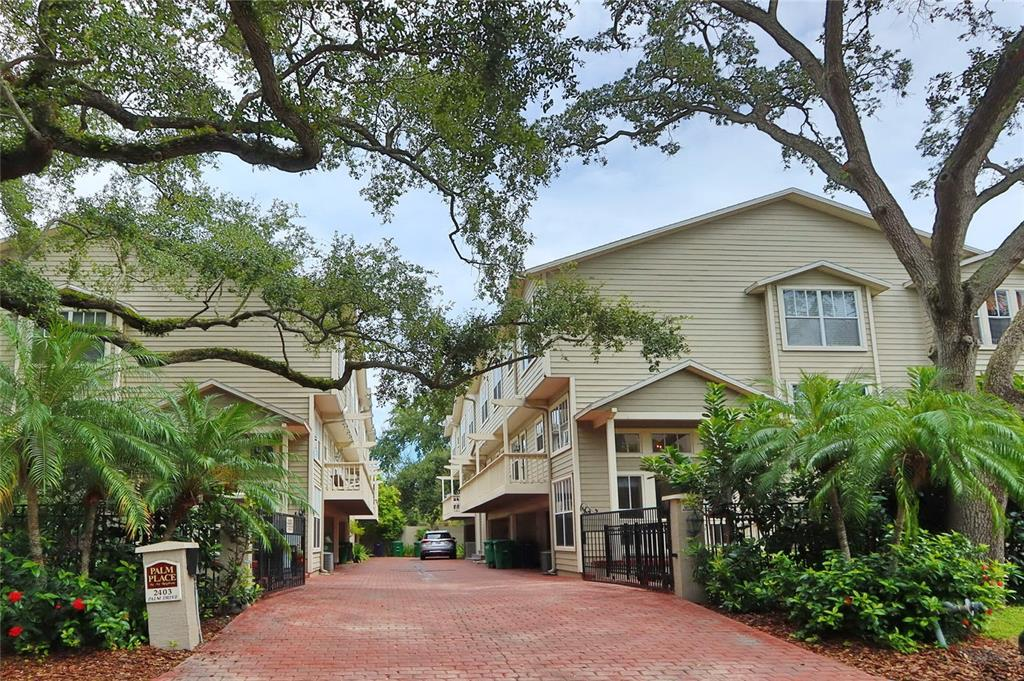 Location, Location, Location! End unit Townhome (1 of 6) with a private courtyard conveniently located steps from Howard Ave and Bayshore Blvd in the small gated Palm Place community offering pavered driveway, large corner fenced yard, and guest parking. Dramatic and unique 3 story floor plan offers bright natural lights, hardwood floors throughout all living areas including all bedrooms, crown molding, fresh paint, and nice window treatments with a spacious two-car garage. The first floor offers a spacious formal entry with a soaring 16' ceiling which steps up to a great room with a wood-burning fireplace, 14' high ceiling, and French doors leading to an outdoor area for relaxing and entertaining. The 2nd floor consists of a large kitchen with all white cabinets, stainless steel appliances, granite countertop, 2 wine refrigerators, a breakfast bar, and an adjoining covered balcony off the kitchen. A separate large dining room for entertaining and a powder bath complete this level. The third floor features all 3 bedrooms with vaulted ceilings, 2 baths, and a laundry closet. The spacious master bedroom can easily accommodate a separate sitting area, a large walk-in closet, and lots of natural lights. The master bath has double vanities, granite countertop, linen closet, garden tub with a separate shower. Both secondary bedrooms are spacious and one bedroom has a walk-in closet and a shared bathroom with granite countertops. No flood insurance is required, you are only minutes to Bayshore, Hyde Park, Downtown, great legendary restaurants, shopping, etc.
