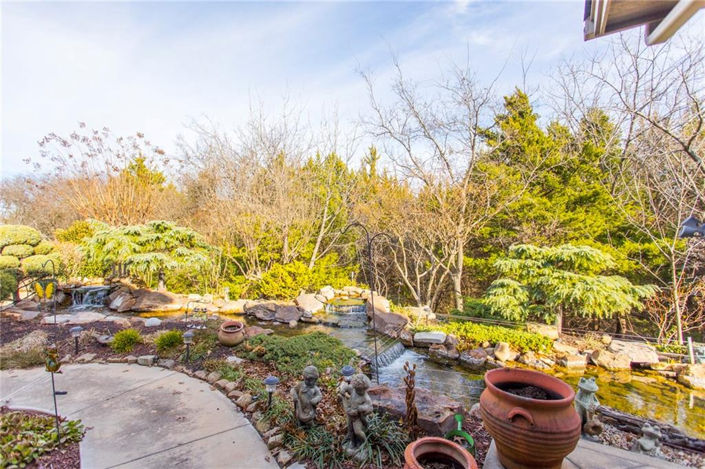 Enjoy a bit of nature in the city!  This lovely traditional home backs up to a beautiful, private wooded greenbelt area with mature oaks & evergreens. You will love this serene & picturesque outdoor setting while enjoying your morning coffee or glass of wine. Great for entertaining! The covered patio w/ wood burning fireplace has a wonderful view of the custom designed 'natural water fall' which flows gently into the unique 24' KOI pond. This one owner custom built home was built with quality construction materials & well taken care of with beautiful hard wood cabinetry, wood work & crown molding. NUMEROUS Upgrades: Plantation Shutters, Granite Countertops, Custom Drapes, New Carpet, Custom Stained Glass Windows, Brand NEW roof! The gardens in spring & summer will WOW you with their beautiful colors from magnolias, various crepe myrtles & hundreds of planted bulbs & numerous bushes! Less than one mile to the Kirkpatrick Turnpike. Open House this Sunday, 2-4pm.  Gates will be open!