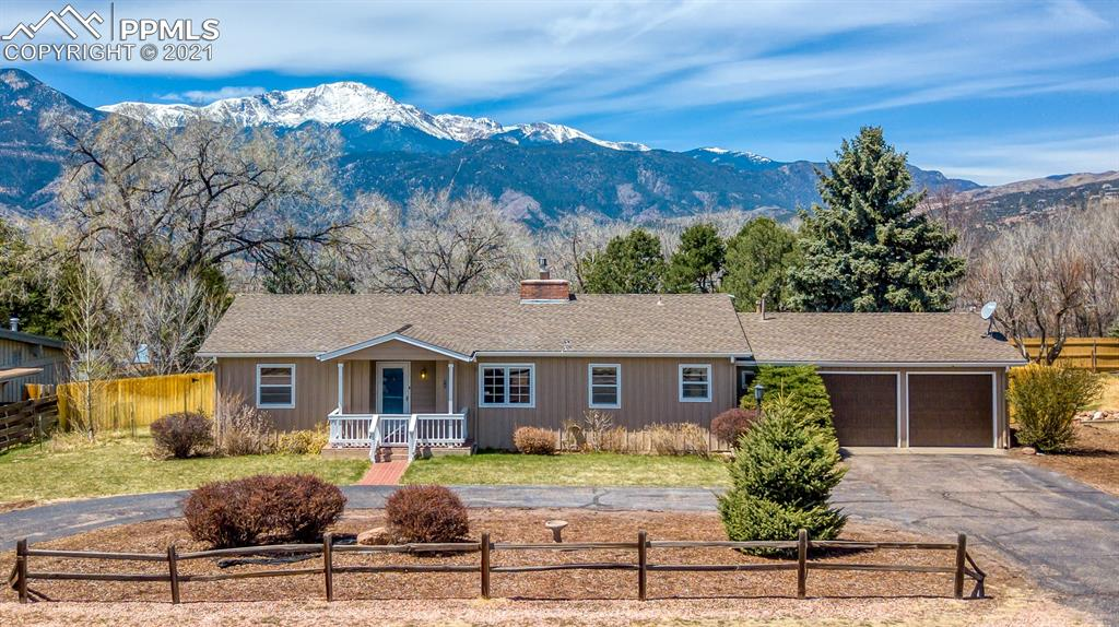 All one level ranch style home on .41 of an ACRE  in a  fantastic area with views of the mountains and Pikes Peak! * Flat and private lot with circular driveway and  extra parking* Tall mature trees* Glowing wood floors throughout most of the home* RV parking possible* Cozy gas fireplace in the great room*Kitchen with eating space* Formal dining open to the living room* Den/office or 3rd bedroom (has pocket door to kitchen) and large picture window*Composite deck*  Lots of  windows in the great room to capture the sunshine and views * Private back yard with mountain views and large (25X20) composite deck with 2 retractable awnings for shade and comfort*  Laundry room with storage* Newer exterior paint* Newer roof * Close to Garden of the Gods, shopping schools, hiking, bike trails, schools* Very quiet area and well cared for home*