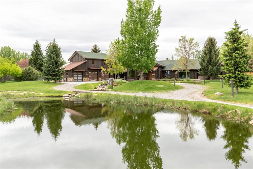 Less than two miles from downtown Bozeman, this custom-designed rustic/modern home seems worlds away in a quiet east side area with spectacular views of Baldy Mountain. Shopping, the hospital and I-90 are just minutes away. This former Parade Home sits on 1.14 acres and includes waterfall, trout pond and separate artist's studio/bunkhouse. Single-level living with vaulted ceiling and timber trusses in the living room, large stone fireplace, radiant-heat concrete floors and spacious loft area. Open kitchen/dining ideal for entertaining, featuring walk-in refrigerator and access to outdoor patio. Master bedroom suite includes walk-in closet and a bathroom, tub, shower and access to patio with outdoor shower. A 22x27 ADU above the heated, oversized, two-car garage has a kitchenette and full bath perfect for guests or rental $. Don't miss the multi-purpose 13x22 Man/Woman Cave which is separate from the main living area. Light covenants, RV parking, electric hookup and fenced back yard.