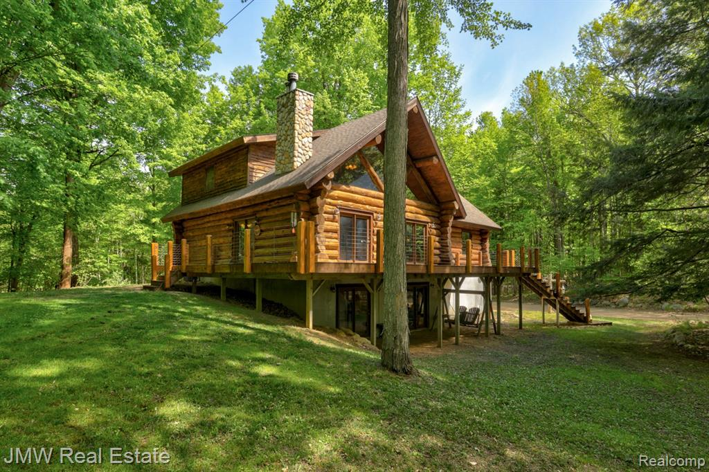 This enchanting oasis is a 10-acre paradise of magical woods, wildlife and a one-of-a-kind log home with an aesthetically matching and hobby-pleasing outbuilding. Large Michigan-harvested timber is fully-scribed making this custom-build a true Lincoln Log style home. Inside, natural light flows through the large windows, illuminating the great room and kitchen on the open-concept first floor. Two bedrooms and a full bathroom can also be found on the main level. The top level is reserved for the pickiest of buyers, offering a massive bedroom, bathroom, walk-in closet, and a flex room that may make a perfect office or even extra bedroom. There's also a balcony that may make a perfect place to sip scotch or drink wine as you watch the wildlife meander through the undulating property. The basement offers a second kitchen, game room, movie theater, and a one-of-a-kind kids playroom. A 40x56 outbuilding is a mechanic's dream, completed with 24x40 loft that could be additional living space.