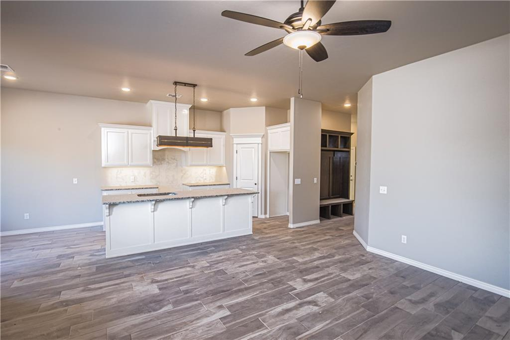 This Teagen floor plan includes 1,715 Sq Ft of total living space, which includes 1,625 Sq Ft of indoor living space and 90 Sq Ft of outdoor living space. There is also a 390 Sq Ft, two car garage with storm shelter installed. Home has a total of 3 bedrooms and 2 full baths. Large family room with a cozy corner gas fireplace, and a large window with lots of natural light. Kitchen has a large island with sink and dishwasher, topped with 2 cm granite, and custom vent hood and cabinetry. Rooms include spacious closets and ceiling fans. The master suite includes a ceiling fan, and a vaulted master ceiling. The master bath includes a walk-in shower, Jetta whirlpool tub, dual countertop vanities, and spacious master closet. The back patio is covered with a wood-burning fireplace, gas outlet for grill and TV hookups. Mudbench installed for extra storage. Other amenities include whole home air filtration system, Rinnai Tankless water heater, R-44 insulation and a TechShield radiant barriery!