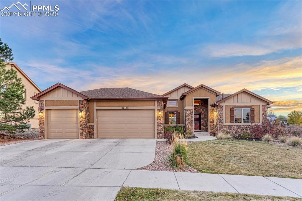 Beautiful One of a Kind Custom Built Ranch Home that Backs to Open Space!!  As you walk in the front door you are greeted with a Giant Great Room with Vaulted Beamed Ceilings and a wall of windows with a view of the Front Range and Pikes Peak! (The South Facing Windows are covered with a UV treatment as well as exterior sun shades.) The covered porch is the perfect place for your morning coffee with easy care composite decking. The Great Room has a Beautiful Stone Gas Fireplace that is the Focal Point of the room!  The Open Kitchen has Granite Counter Tops, Stainless Steel appliances, Convection Oven and an Electrolux Chef Gas Range/Oven. The floors on the main level are Hand Scraped Plank Hardwood which showcase the Custom Knotty Alder Cabinets, Doors and Crown Molding.  The Master bedroom is complete with a 5 piece bathroom, tile floors, and Walk-In Closet!  There are 2 additional bedrooms on the main level which can be transformed into His & Hers Offices....Covid Classrooms....or anything you want them to be!  Off of the 3 Car Garage is a large Mudd/Laundry room complete with a Washer/Dryer Set (Included)
