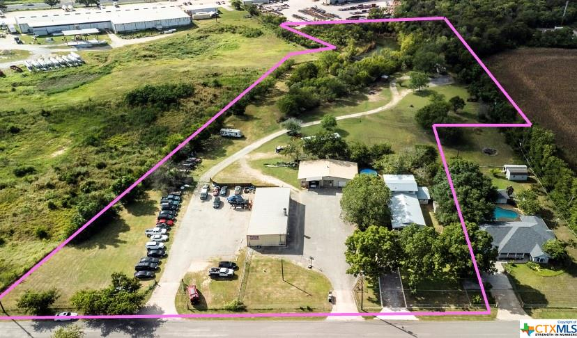 Revenue-generating 6.44 acres surrounded by planned developments (More Details On Flyer) *Unique Opportunity* Property has (2) commercial buildings and (1) single family residence. Multiple highest and best uses! As an owner, you can live here, work here, AND produce a monthly income! (1) 2,800 sqft leased metal building consists of (3) bays: 34x42 shop + 20x20 open bay + 20x20 office : (2) 2,196 sqft building owner occ. consists of (3) bays: 21x36 open bay + 18x36 office + 20x36 oversized garage : (3) 2,408 sqft beautifully remodeled 2 story home w/ 3bd/2ba. Charming modern-rustic vibe with wood-laminate and tile flooring, two living areas, bonus room, and a steel spiral staircase leading to the upstairs suite featuring a spacious covered deck. Includes 3 septic systems, 3 water meters, and 5 electric meters. City website shows progress for a wastewater line 0.5 miles on I-35. Future extension along Post Road is likely to fuel the 180-acre mixed use development across the street.
