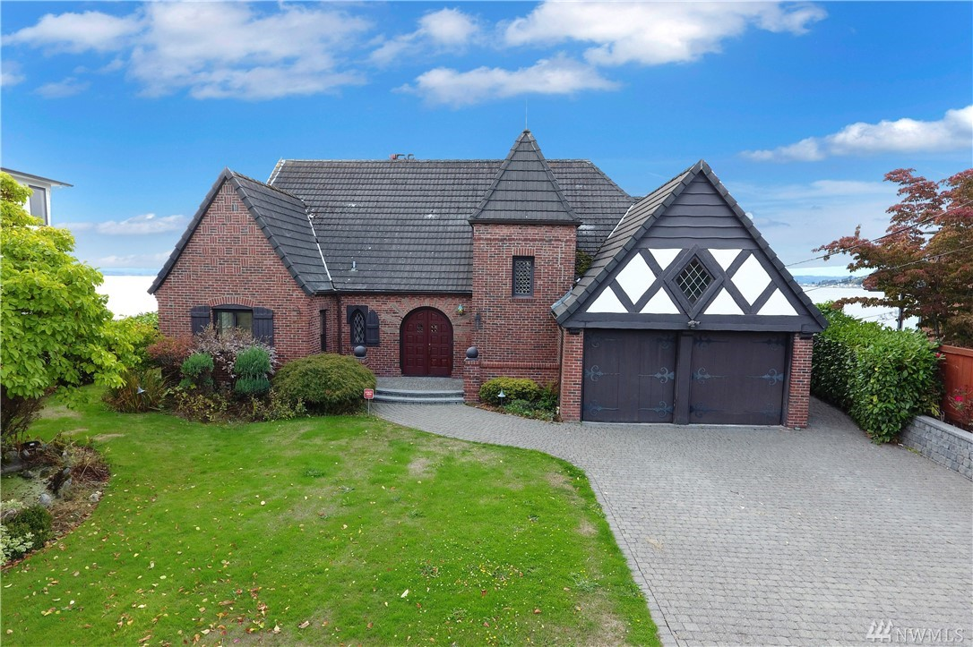Low Bank Waterfront! Historic French Normandy style chateau crafted in 1929. This lovely home sits on 94 ft of low  bank waterfront with bulk head. Refurbished with master craftsman details, including a cobblestone driveway, walking  paths to the beach, copper gutters, hardwoods throughout, cove ceilings, impressive fireplace, hand painted wall art,  designer kitchen and slate patio. Enjoy Puget Sound waterfront living ,watch eagles soar, Blue herons feed, whales, seals  and otters playing!