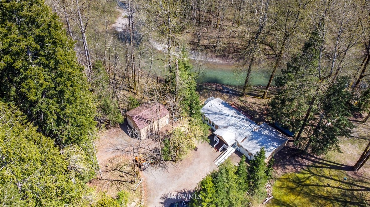 Looking for river front property in Packwood? Look no further. This is the perfect recreational getaway or retreat to call home! This double parcel lot just under 1 acre has it all! Come enjoy the sound and views of the river in your backyard while just minutes from town. This over 1,500 square foot home has 3 bedrooms and 2 full bathrooms with open concept living perfect for entertaining. The second lot has a large metal detached shop with parking for up to 4 cars or an RV. The attached garage gives you a total of 6 covered parking spots. There are 2 RV hookups on the property.  High Valley HOA includes golf, pool and playground.  Close to White Pass ski resort, national parks and a river in your backyard there is fun to be had year round!