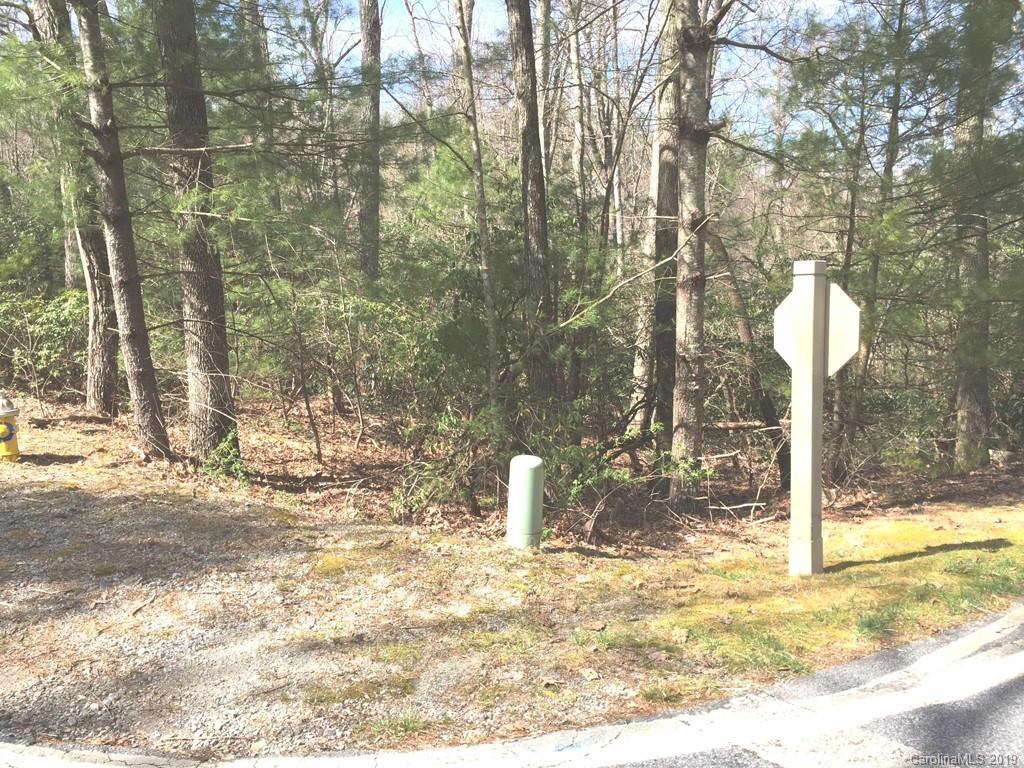 Kenmure gated community home site with gentle topography, hardwoods, and a creek/stream awaits your dream home.