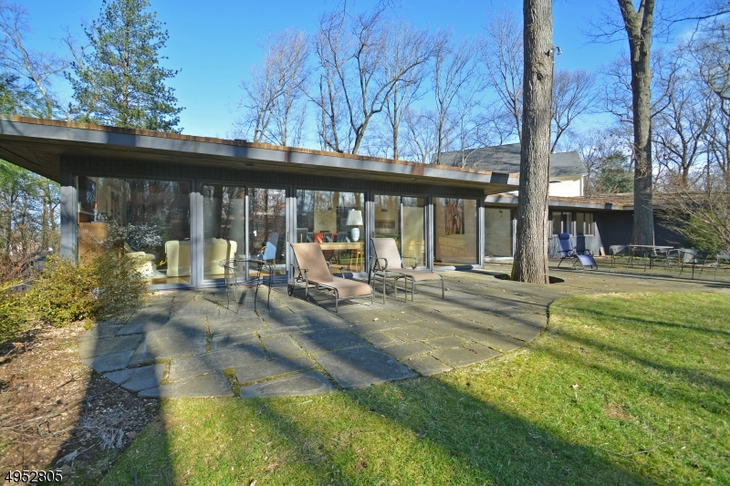 This amazing Mid Century Modern home set on .96 acre of private property was built by the homeowner in 1962. Here is an opportunity to be the 2nd occupant of this one of a kind, well-maintained home. One story living with a great floor plan and tons of natural light. So much attention to detail throughout; including Andersen gliding windows, living room fireplace with gas starter, St Charles kitchen cabinets, indoor grill with professional grade hood, two zone HVAC and home backup generator.Two car garage on grade, plus a separate additional garage. 1st floor includes 4 BRs, a den/5th BR, an open living/dining area, kitchen with sitting area and mudroom with laundry and garage entrance. Every room has beautiful views of the wooded property. This property is not to be missed!