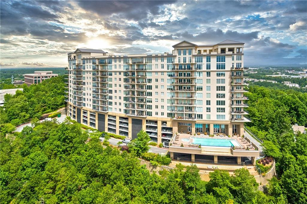 Fabulous condo available at One Vinings Mountain located on the 10th floor. This elegant unit offers floor to ceiling windows with panoramic views to the city of Atlanta. Come home to elegance and the extras of luxury condominium living including upgraded stainless appliances, hardwood floors in the kitchen, living and dining room, lush carpet in both bedrooms, granite finishes in the kitchen and master bath, completely remodeled kitchen, private balcony, built in desk and file drawers, built in Murphy bed, and a spacious open floor plan. Located in Cobb County, it