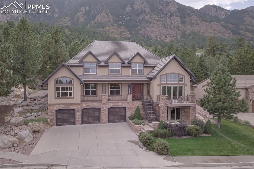 Truly amazing views of Cheyenne Mountain and unobstructed sunrise in this custom high-end open concept home located at the base of the mountain.  Several features which inspire this comfort living at the base of the mountains start on the exterior with beautiful mature landscaping surrounding the house.   The quality of construction and attention to detail and extras are found throughout.   Multiple maintenance free decks including several covered areas to enjoy the beauty and views of the neighborhood outside as well as through the many windows in every room.   Interior features include elevator access to all floors that requires no steps entrance from garage, a walk out basement with an exquisite walk behind wet bar, with 9' ceilings throughout adjoining rooms with vaulted ceilings, 5 car oversized heated garage, automatic fire system and security alarm.   The well designed kitchen includes stainless steel appliances including double oven, separate island with gas cook top, and multiple seating areas which include the dining nook in kitchen, at the bar island between kitchen and living room, or in the formal dining room which is accented with recessed ceiling.   Enjoy working from the main level office which has stone accent walls and built in bookshelves and cabinets.  The Master bedroom is a soothing retreat that includes walk around fireplace with sitting area, large attached bathroom with radiant floor heating, a jetted tub as well as a full walk in shower, double vanities, and a large walk in closet.   The upper level has a large Jack and Jill bathroom with double vanities separating two large bedrooms that have views of the city.     Two additional bedrooms are also located upstairs.