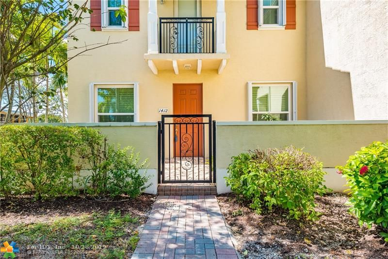 Look no further! Mrs. Clean lives here! This corner unit features impact windows and doors with additional accordion shutters for extra protection. Patio sitting area features custom tranquility waterfall for extra relaxation. Step inside the immaculate home and notice the open layout with tray ceilings and new tile throughout. Home was also freshly painted with newer crown moldings, lovely window treatments  and undated light fixtures. Newer open kitchen with stainless steel appliances and custom coffee bar. Lower level bedroom currently used as Den and fully remodeled bathroom. Upstairs feature 3 bedrooms with carpet and laminate flooring. Laundry room on second floor with newer GE High efficiency washer and dryer. Large master bedroom with large walk in closet finishes this lovely home.