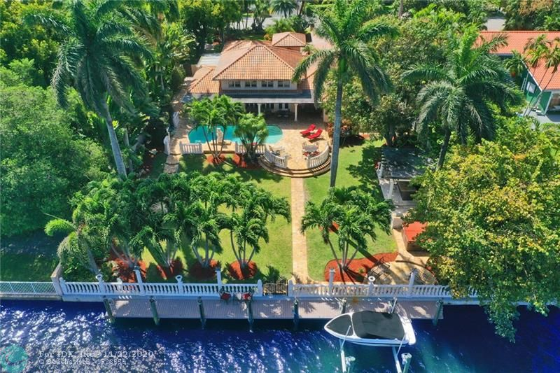 Located on a quiet tree lined street in Hollywood Lakes, elegant 1 story custom estate surrounded by tropical landscaping. Private 1/2+ acre corner property, 100' water frontage, 75' deep water dock, w/boat lift a boaters paradise, no fixed bridges. View 360° Virtual Home Walkthrough Tour, just copy paste: https://bit.ly/2vHSX9c or view Drone View: https://bit.ly/2xdQqUu Electric/accordion hurricane shutters, newer AC. Enjoy the magnificent water views from the Loggia surrounding the pool. Outdoor fountains, wet bar, Pizza oven, lounging areas evoke a feeling of resort style living at its best. Living room has a custom bar w/etched glass paintings, Kitchen has 6 Burner commercial grade gas stove, granite counter tops. Large master suite has hard wood floors, Master bath has steam shower